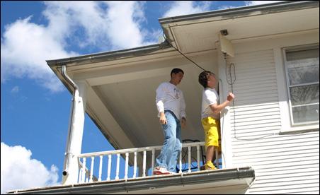 Tyler Erickson and George Rogotzke right the antenna on the Swenhaugens' white frame farmhouse.