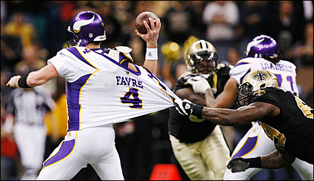 Brett Favre throws a pass as New Orleans Saints Anthony Hargrove pulls on his jersey during the fourth quarter of the NFC Championship game.