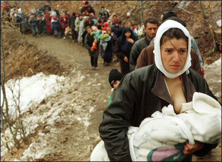 An ethnic Albanian woman feeds her baby as she and another 2,000 refugees walk to Macedonia, March 30, 1999.