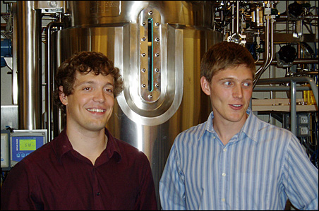 Alex Johansson and Joe Mullenbach stand in front of bio-fermentation tank at the University of Minnesota.