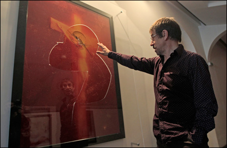"""Jean Marc Ferrari, Museum of Fine Arts director, assesses the damage to """"Piss Christ"""" by activists on Tuesday."""