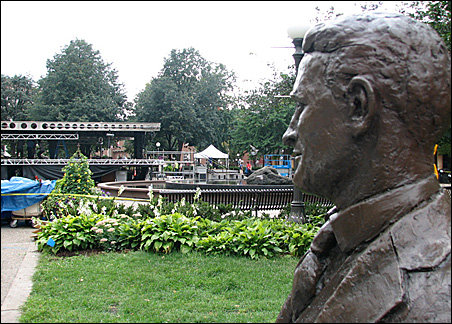 From a perch in the corner of Rice Park, the F. Scott Fitzgerald statue overlooks setup work on the MSNBC stage.