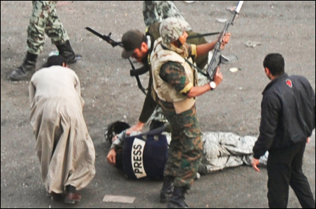 A member of the press lies on the ground after being attacked by mobs while soldiers surround him in Cairo.