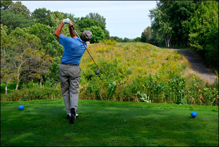 Roger Buoen hits a drive over a wildflower-filled ravine toward the fairway on the 16th hole (old No. 7).