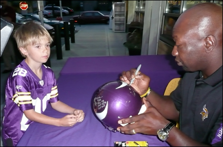 Former Viking John Randle signs a helmet for Ian Olson during the event.