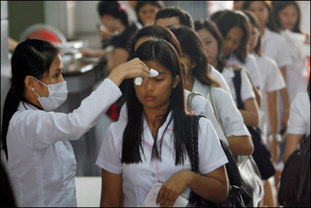 Precautions against the new flu strain are being taken worldwide. Here, health workers at Centro Escolar University in the Philippines take students' temperatures in June on the first day of school.