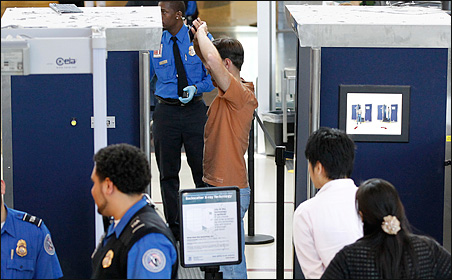 A man being screened with a backscatter X-ray machine at a TSA security checkpoint at Los Angeles International Airport.