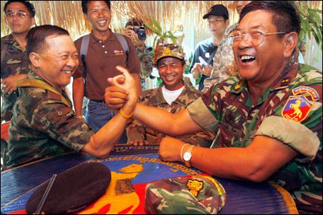 Cambodia Major General commander Srey Dek, right, arm wrestles with Thai Major General Kanok NetraKaveysana, left, during a joint lunch at Koe sekhakirisrarak pagoda near Preah Vihear temple April 5, 2009.