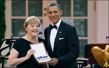 President Barack Obama presents the Presidential Medal of Freedom to German Chancellor Angela Merkel at an official State Dinner in the Rose Garden on Tuesday.