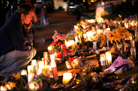A man looks over the memorial outside the hospital where victims of Saturday's shootings are recovering in Tucson.