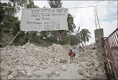"""A """"We need help"""" sign hangs outside a destroyed slum in Port-au-Prince."""