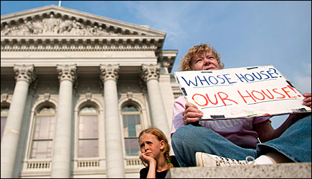 A protester holds a sign outside the Wisconsin State Capitol earlier this summer.