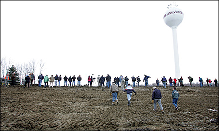Residents gather on a levee to watch National Guard Blackhawk helicopters drop sandbags in Fargo on Sunday.