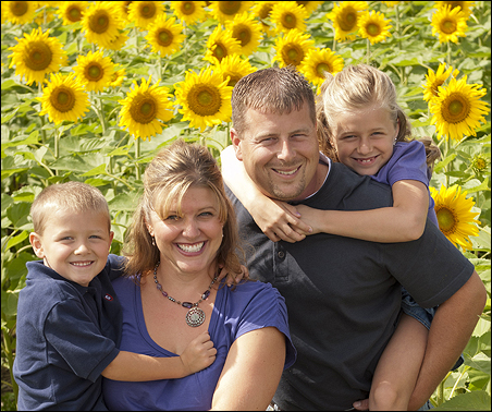 Tom Smude with his wife Jenni and their two children on their farm near Pierz, Minn.
