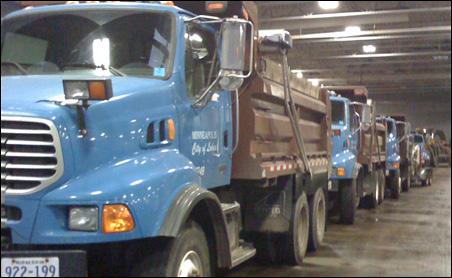 Dozen of Minneapolis snow removal trucks stand at the ready.
