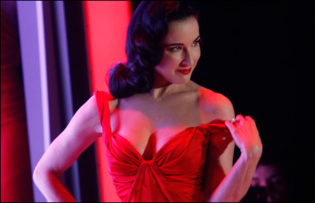 Burlesque artist Dita Von Teese presents a creation from Zac Posen during the Heart Truth's Red Dress Collection 2011 Fashion Show.