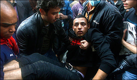 An injured protester is carried away by others during clashes in Cairo.