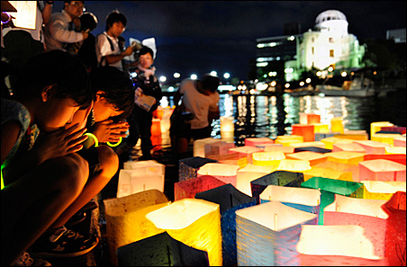 Girls pray after releasing paper lanterns on the Motoyasu river in remembrance of atomic bomb victims on Friday.