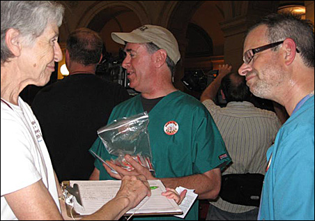 Minnesota Health Plan advocate Bernice Vetsch asks Tom Kelly, right, of the Minnesota Nurses Association to sign a petition Wednesday in the Capitol rotunda before the Mad As Hell Doctors rally begins.