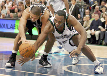 The San Antonio Spurs' Tim Duncan and the Timberwolves' Al Jefferson battle for the ball during a February game.