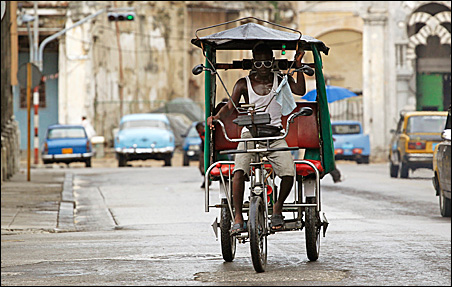 A man looks for customers as he rides his bicycle taxi in Havana on Wednesday.