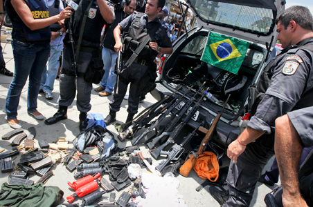 Police show drugs, weapons and hand grenades which were confiscated, a day after invading the Alemao slum in Rio de Janeiro.