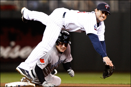 Minnesota Twins Nick Punto watches his throw to first base to complete a double play as he leaps over Toronto Blue Jays Travis Snider.