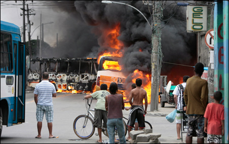 Two public buses are set on fire by drug gangs trying to distract the police from their battle for the control of a slum in Rio de Janeiro over the weekend.