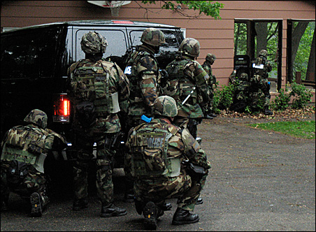 A SWAT team prepares to enter the Scolls' house.