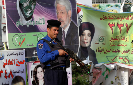 An Iraqi policeman stands guard in front of election posters in Baghdad on Wednesday.