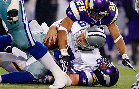 Dallas Cowboys quarterback Tony Romo is sacked by Tyrell Johnson and Chad Greenway during the third quarter.