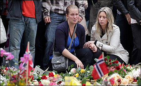 Mourners pay their respects near floral tributes placed outside the Oslo Cathedral on Monday.