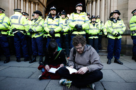 British student protesters sit in front of police officers during a demonstration against planned tuition hikes.