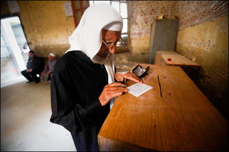 An Egyptian man fills in his ballot at a polling station during the runoff of the parliamentary elections in Cairo.