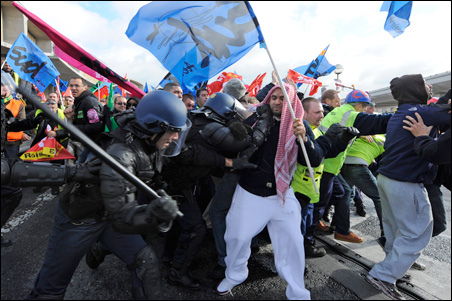 French striking workers clash with police as they block the Charles de Gaulle airport in Roissy near Paris on Wednesday.