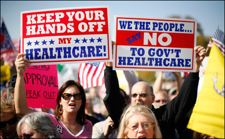 """Demonstrators hold signs during a """"House call"""" rally against proposed healthcare reform legislation at the Capitol Thursday."""