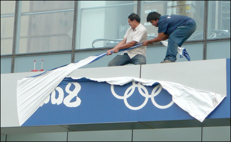 Workers wasted no time taking down some Olympic signage following the conclusion of the Games.