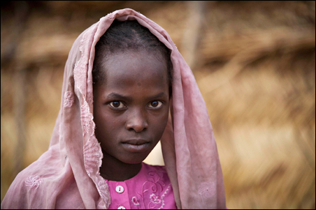 A young refugee from western Darfur stands outside a shelter in the Djabal camp in eastern Chad in June, where an estimated 250,000 Sudanese refugees are scattered throughout a dozen camps.