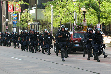 Riot troops hustle south on Wabasha Street, near Fifth, after pockets of protesters tangled with authorities.