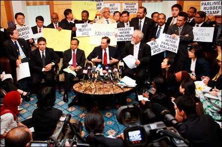 Malaysian opposition leader Anwar Ibrahim (C) and other opposition leaders talk to the members of the media as they hold protest placards at the parliament lobby in Kuala Lumpur.