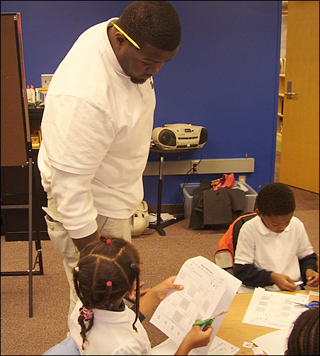 Teacher Darius Lyles helps Favor Osojuri while De'Angelo McKinley concentrates on a worksheet.