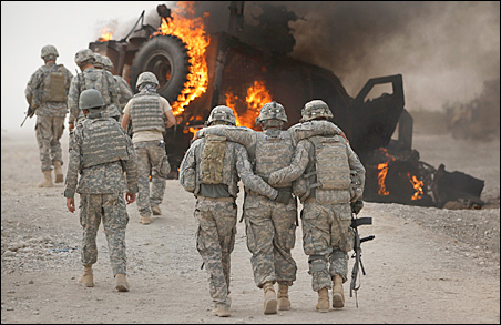 A soldier with an injured ankle from the the 1-320 Field Artillery Regiment, 101st Airborne Division is assisted past his burning M-ATV armored vehicle after it struck an IED on a road near Combat Outpost Nolen in the Arghandab Valley on Friday.