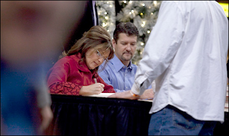 Sarah Palin, with an assist from husband Todd, autographed books today at the Mall of America.
