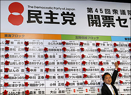 Japan's main opposition leader Yukio Hatoyama places a marker on a winning candidate's name at the Democratic Party of Japan election headquarters in Tokyo.