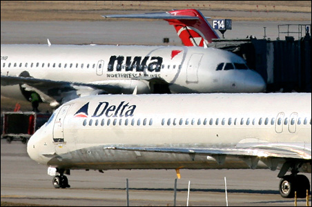 A Delta Air Lines jet taxis past a Northwest Airlines jet parked at a gate at the Minneapolis-St.Paul International Airport Monday. The pending Delta-Northwest merger would create the world's biggest airline.