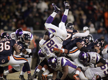 Vikings running back Adrian Peterson dives over a pile of players for a first down against the Chicago Bears in the fourth quarter of Monday night's game.