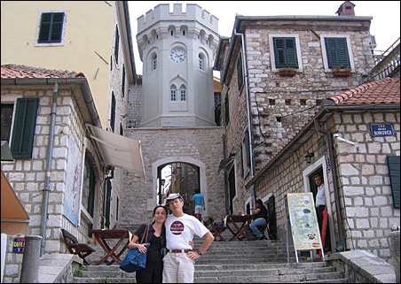 Greg Filice, wearing his new MinnPost T-shirt, poses with his wife, Svetlana Simovic, in front of the clock tower in Montenegro, Serbia.