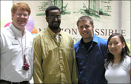Jim McCorkell with Admission Possible graduates, from left to right, Abdihamid Geyre, Brendan Ireland and Lily Moua.
