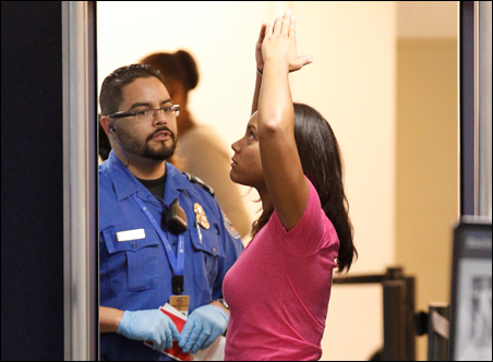 A Transportation Security Administration screener scans a passenger at Fort Lauderdale-Hollywood International Airport on Tuesday.