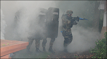 A smoke grenade is set off to screen a SWAT team as it enters the house.